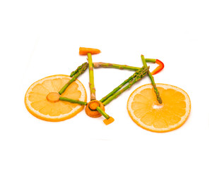 Top view symbolical road bicycle made from different fresh raw vegetables and fruits isolated on white. Symbol and sign for vitality and healthy lifestyle, full of vitamin food concept. Be fit, strong