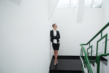Young caucasian woman standing on the stairs in the office.