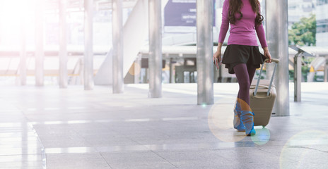 woman traveler walking with suitcase at airport corridor