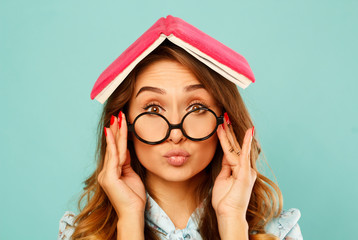 Beautiful young student holding book on her head and wearing glasses over blue background