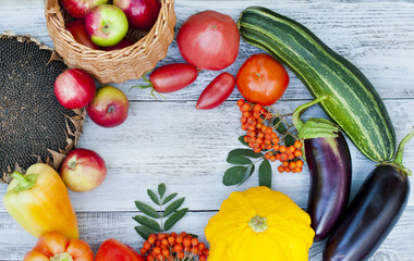A set of ripe vegetables on a wooden background, a crop of apples, tomatoes and aubergines, agriculture.