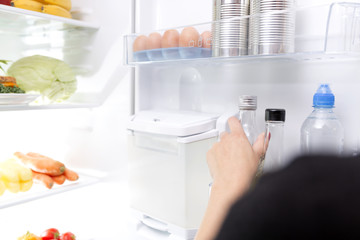 Woman taking a glass bottle out of the fridge