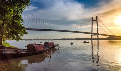 Foto op Aluminium Rivier Wooden boats at the river bank at sunset overlooking the famous Vidyasagar Setu bridge