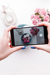 From above unrecognizable person taking shots of sweets and flowers with smartphone. Food photography for social media
