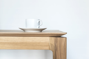 Image of a white porcelain coffee cup on a modern style oak wooden table