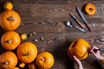 Hands carving jack-o-latern from pumpkin over wooden background, top view, flat lay Wall mural