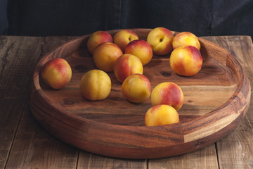Nectarines lie on a wooden platter