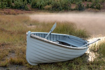 White rowboat on bank of lake on a misty morning
