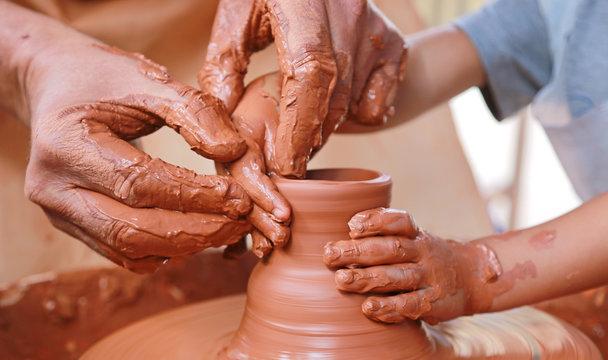 manos barro alfarero enseñando a un niño U84A1128-f17
