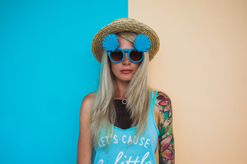 Beautiful young woman hipster with a tattoo in sunglasses and a hat on a bright coloured background. Beach style