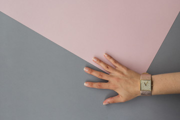 Female hand and wristwatch on gray pink geometry background