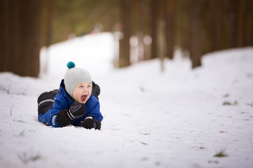Portrait of cute toddler in warm winter clothes laying on the snow and smiling. Child walking in winter forest. Lifestyle concept