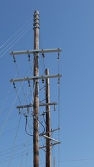 Wooden power utility pole with transformers and cables.