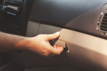 Male hand opens the glove compartment in the car, retro toning