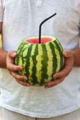 A young man holds a whole watermelon with a straw for drinking, a cocktail. The concept of healthy nutrition and vegetarianism