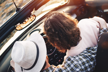 Loving couple in modern cabriolet at sunset. Happy couple traveling on convertible car