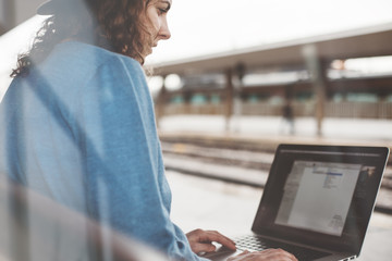 Young girl is waiting for a train at railway station and sits with laptop