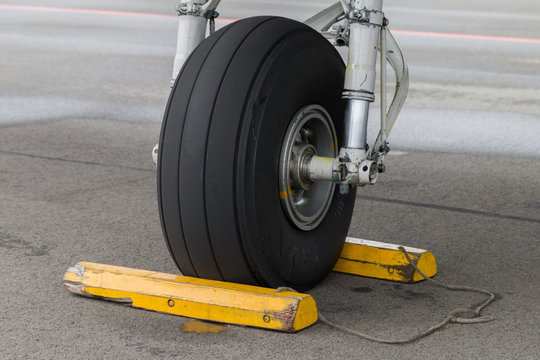 Closeup of aircraft front gear, tire with yellow chocks