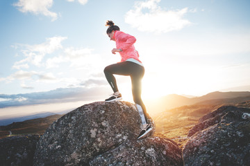 Sports girl running in the mountains at sunset against the backdrop of a beautiful landscape. Sport tight clothes. Intentional motion blur.