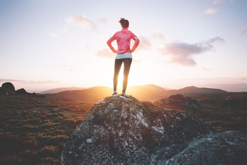 Athletic woman examines mountain landscape for training on running at sunset. Sport tight clothes.
