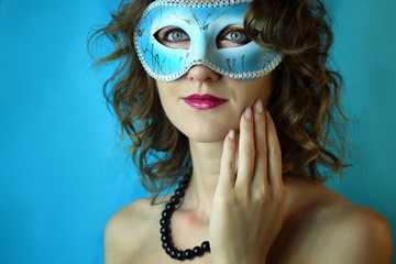 Beautiful young woman in mysterious blue carnival mask. Fashion and beauty photo