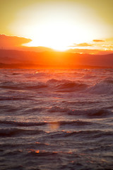 Sunset in the waves. Reflection of sun rays in the lens effect. Abstract image for background