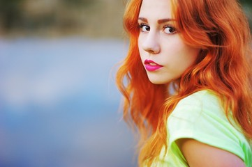 Wonderful portrait of a beautiful brown-eyed girls with bright red hair and bold makeup in the Park by the lake in the summer.