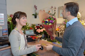 florist and male customer smelling flower bouquet at store