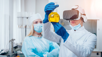 Science technician in virtual reality glasses examines the drug in laboratory.