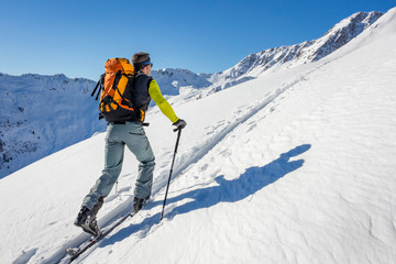 Male ski tourer hiking in the alps
