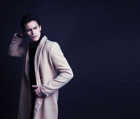 cool real young man in coat on black background
