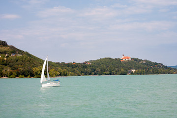 Tihany Peninsula with the Abbey and a sailboat viewed from a ship's deck