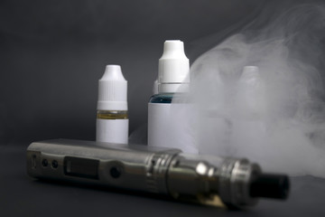 electronic cigarette, vape device next to  e liquid bottles and tools.