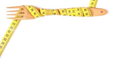 Wooden fork wrapped tape measure, concept of slimming, copy space for text on white