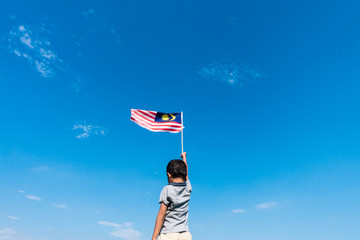 Unknown kid waving Malaysia Flag. Independence day and Merdeka Celebration. Blue sky and copy space.