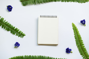 Creative Flat lay design of blank notebook with green leaf on white background.