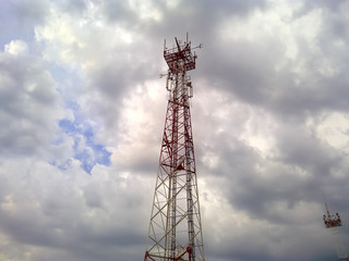Cellular tower. Telecommunication tower. Communication tower against the sky with clouds.