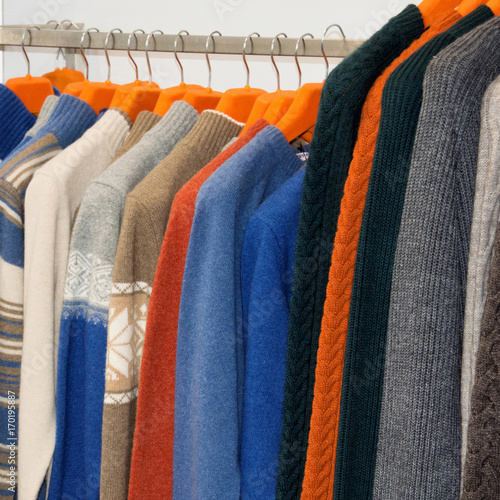Nice warm colorful sweaters hang on hangers inside of a shopping mall. Beautiful  clothes for winter autumn season. Fashion industry for men. 60b1c1f88