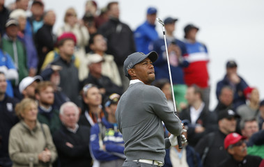 Woods of the U.S. watches his tee shot on the eighth hole during the first round of the British Open golf championship on the Old Course in St. Andrews, Scotland