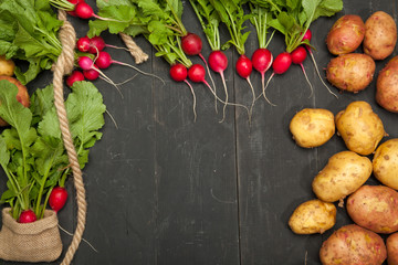 Raw radishes, onions and potatoes on a black wooden background