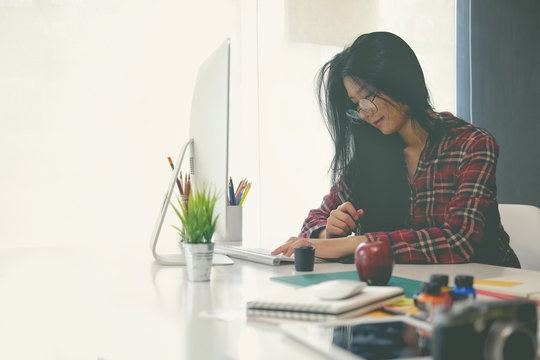 Young asian woman working in office, sitting and using desktop computer at white desk.