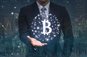 Businessman hand holding the bitcoins text financial technology or FINTECH connection over the digital number and trading graph background, Showing the cryptocurrency or digital money