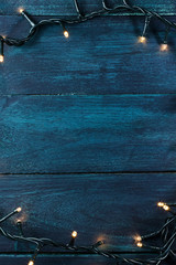 Fairy lights on a dark wooden texture, holiday background