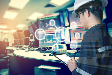 Double exposure of Engineer or Technician man with business industrial tool icons while using tablet with monitor of computers room  for oil and gas industrial business concept