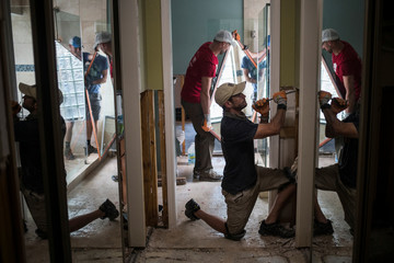 Samaritans help clear debris from the house of a neighbor which was left flooded from Tropical Storm Harvey in Houston
