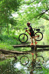 Young asian biker crossing the river with her bike in her hand