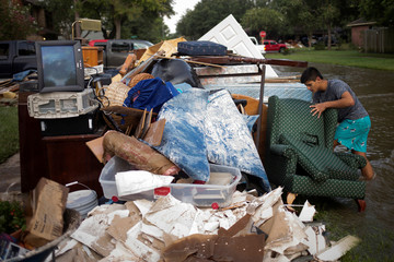 Man helps discard furniture from house of neighbor who was left flooded from Tropical Storm Harvey in Houston
