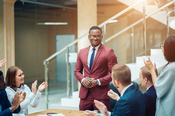 smiling black male boss talking to business team