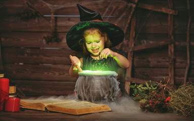 Halloween. little witch child cooking potion in   cauldron with spell book