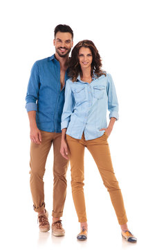 full body picture of young casual couple standing and smiling
